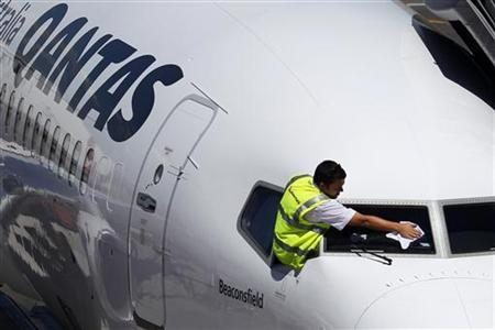 Ground crew member cleans the windshield of a Qantas passenger plane at Adelaide airport